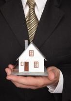 businessman holding model home